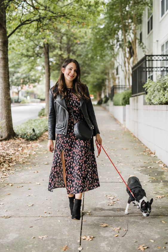 a dark moody midi dress, a black leather jacket, a round bag and suede booties