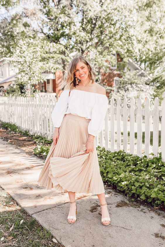 a romantic spring look with a white off the shoulder blouse, a tan pleated midi, nude shoes