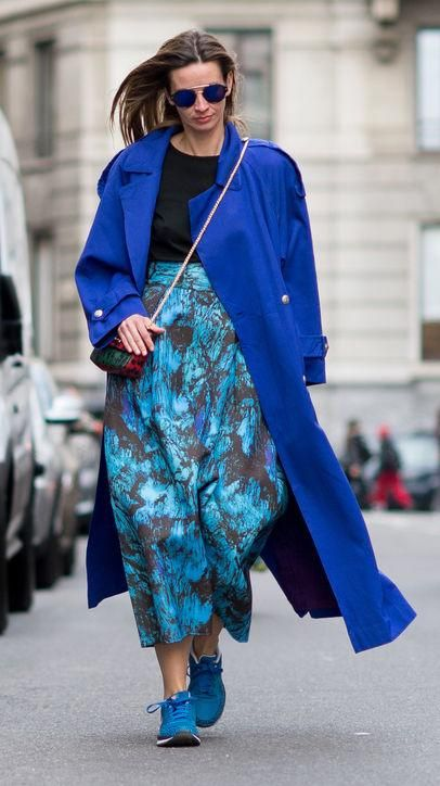 a classic blue midi coat, a turquoise printed skirt and matching trainers for a bold winter look