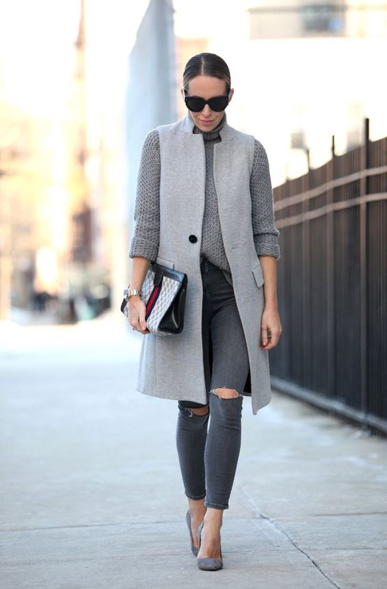 a monochromatic grey outfit with a turtleneck sweater, grey ripped skinnies, shoes and a grey sleeveless coat