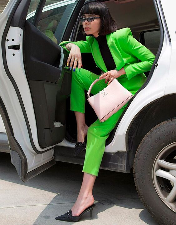 a neon green pantsuit, a black turtleneck, black mules and a pink bag for a spring work look
