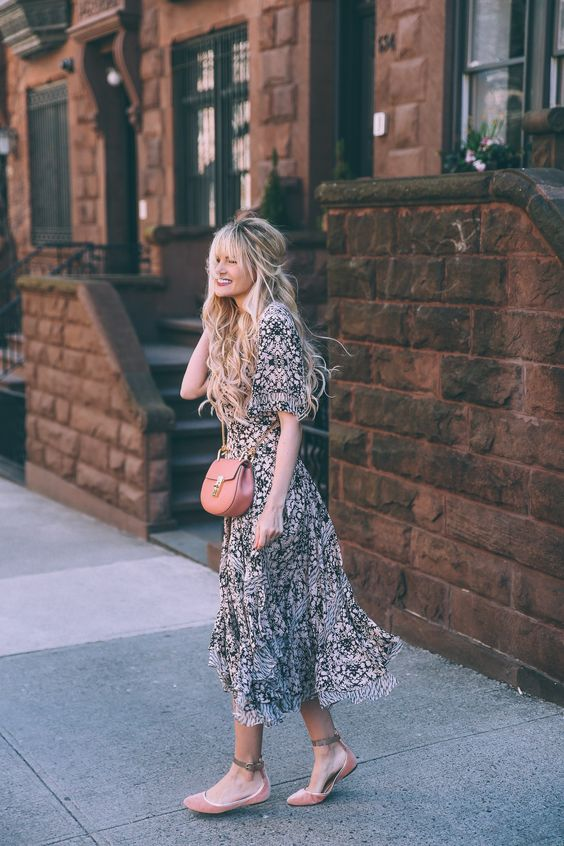 a romantic black and blush midi floral dress, a pink crossbody and pink suede flats
