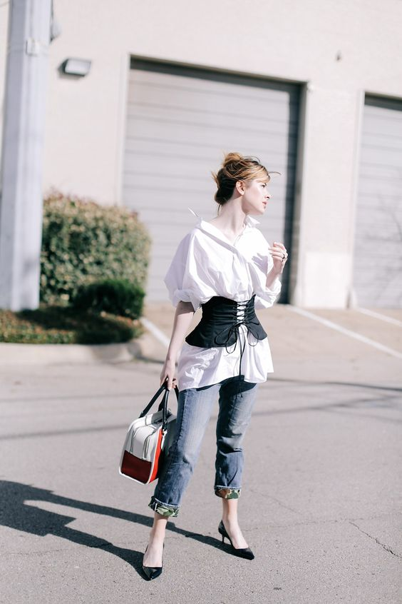 blue jeans, a white oversized shirt, a black corset belt, black shoes and a whimsy bag