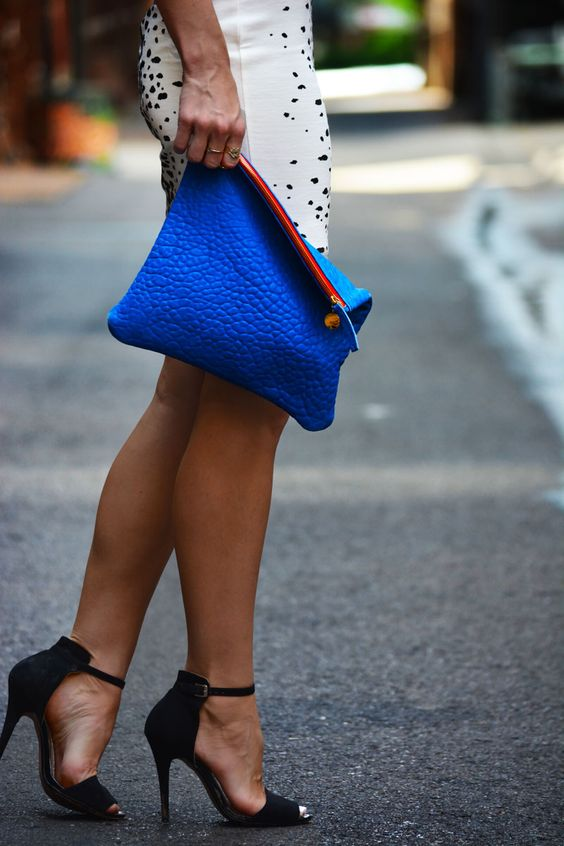 a classic blue clutch with a pink zip is a stylish touch of color to your neutral or monochromatic outfit