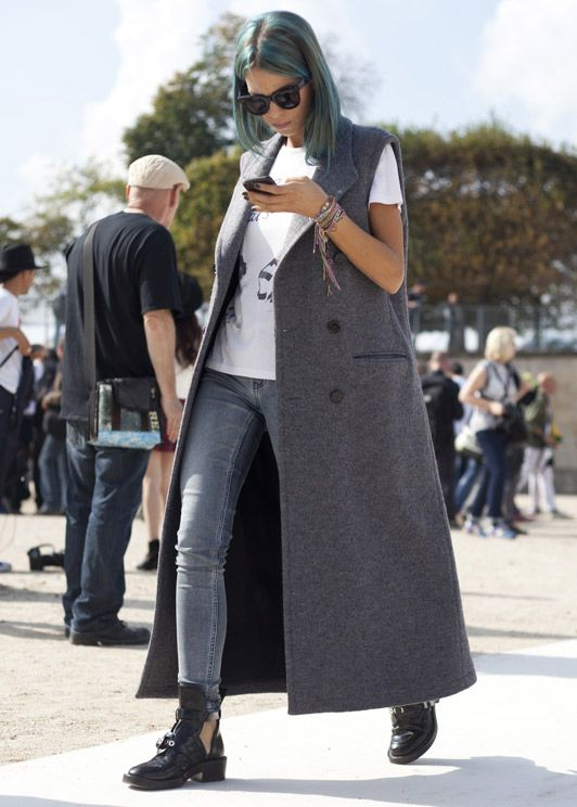a printed tree, grey jeans, black cutout boots, a grey maxi sleeveless coat