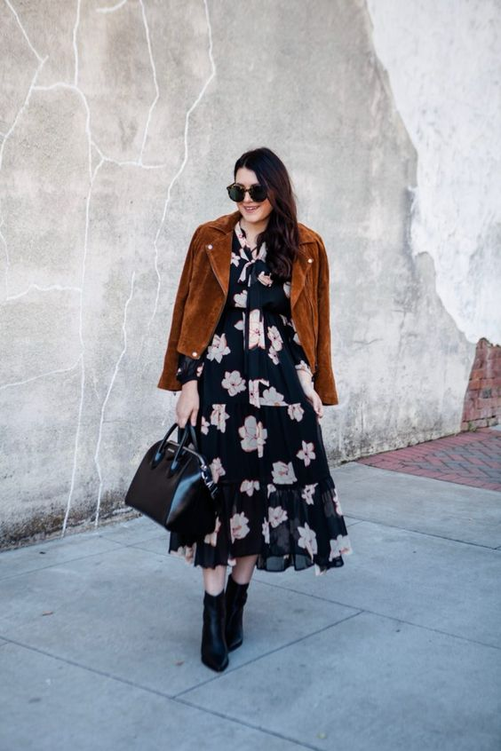 a black floral midi dress, black booties, a black bag and a rust-colored suede cropped jacket