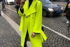 06 a bold outfit with a black turtleneck, black skinnies, a neon green coat, a black bag and white, black and neon trainers