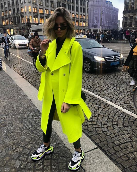 a bold outfit with a black turtleneck, black skinnies, a neon green coat, a black bag and white, black and neon trainers