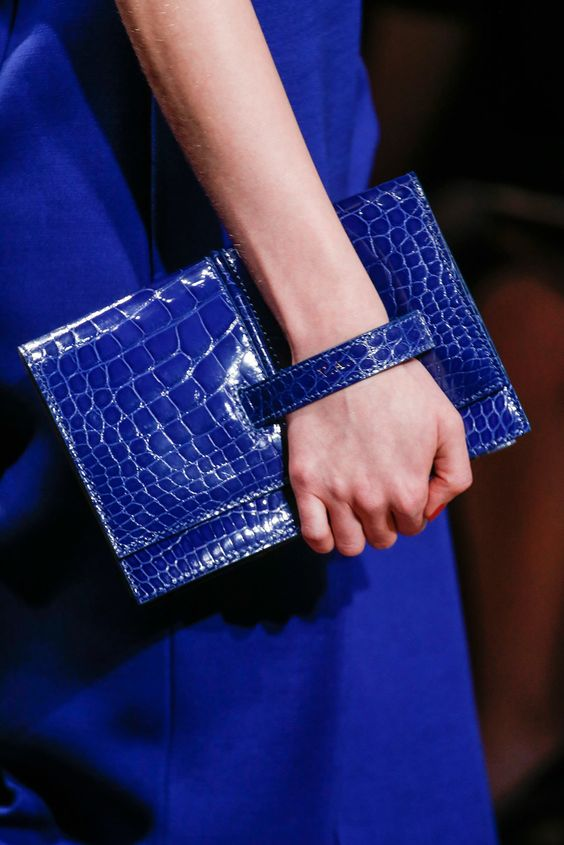 a classic blue crocodile leather clutch with a handle is a cool and chic fashion statement for this year