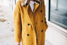 06 a mustard yellow coat, a white tee, blue jeans, a grey beanie and a brown bag