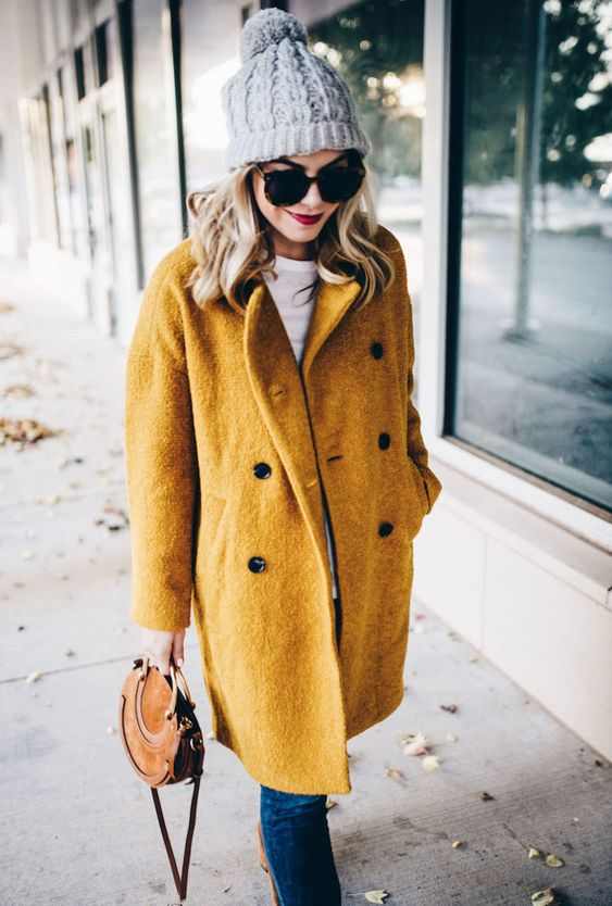 a mustard yellow coat, a white tee, blue jeans, a grey beanie and a brown bag