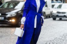 07 a long classic blue coat worn with a simple black and white outfit to add a colorful touch to it