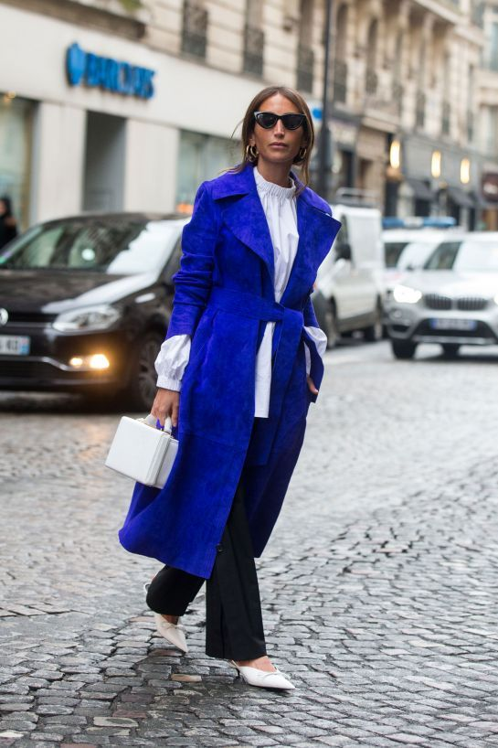 a long classic blue coat worn with a simple black and white outfit to add a colorful touch to it