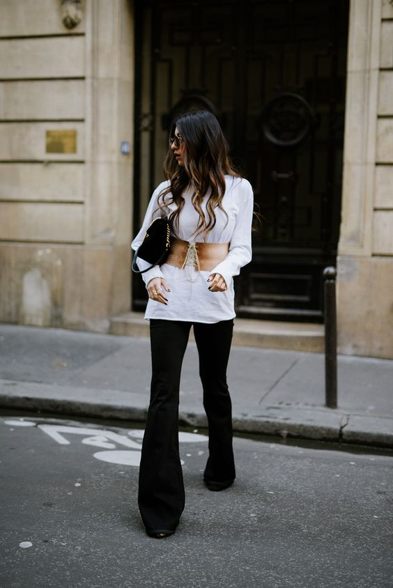 a white shirt, black pants, a brown corset belt and a black bag for a trendy spring look