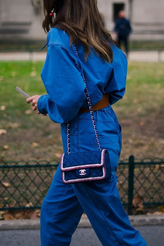 a classic blue jumpsuit paired wiht a tiny matching bag with embellishments and embroidery by Chanel