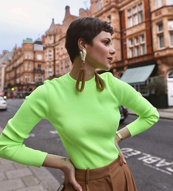 a neon green top, brown pants and statement earrings with brown detailing for an edgy look