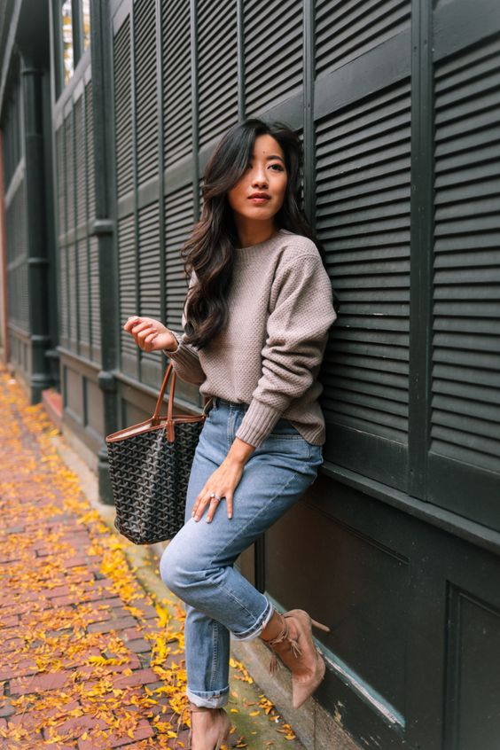 a neutral oversized sweater, light blue straight jeans, taupe shoes and a printed bag