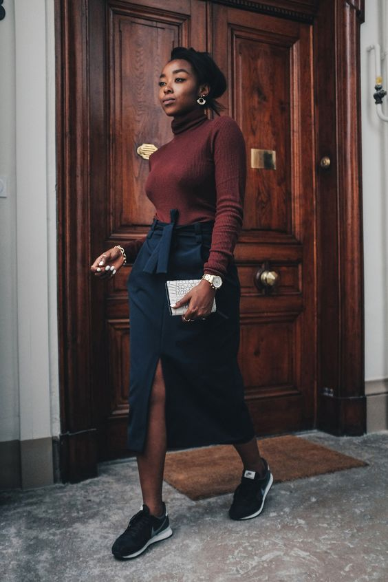 a brown turtleneck, a navy midi skirt with pockets, black trainers and a white snakeskin clutch