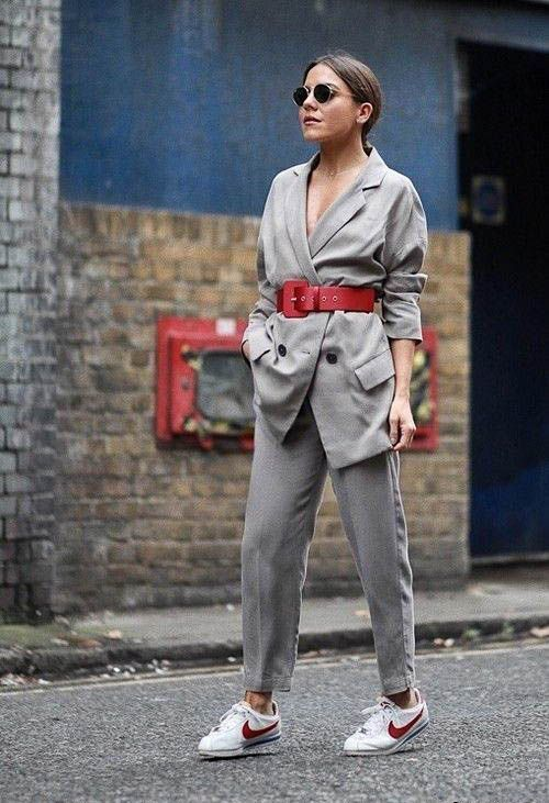 a grey pantsuit, a red wide waist belt and two tone sneakers for an ultra modern and bold look