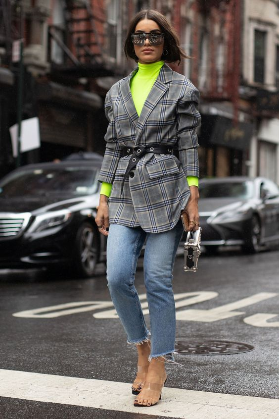 a neon green turtleneck, blue straight jeans with a raw hem, an oversized checked blazer and a silver bag