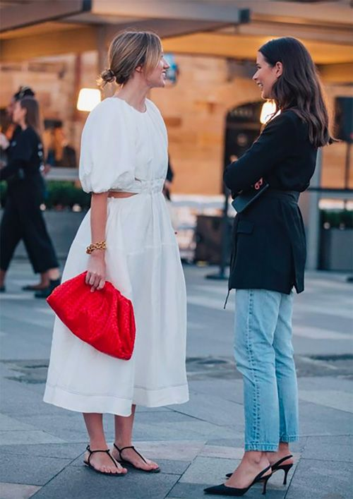 a light and romantic white midi dress paired with a hot red soft clutch for a colorful statement