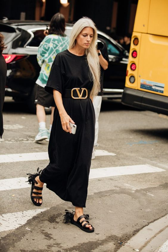a minimalist black maxi dress with short sleeves and a high neckline is accented with a wide waist leather belt with a bold buckle