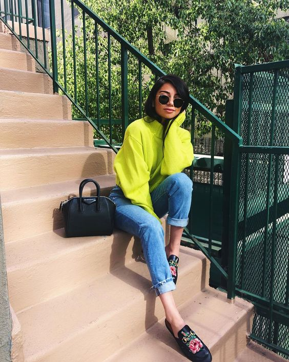a neon yellow sweater, blue mom jeans, floral mules and a black bag for spring