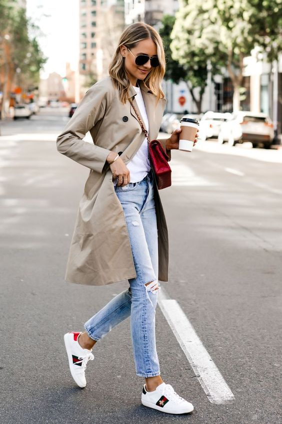 a white tee, light blue ripped jeans, white sneakers, a neutral trench and a red bag