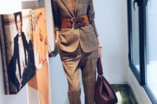 11 a neutral plaid pantsuit accented with a brown leather belt and a statement accessory for a bold look