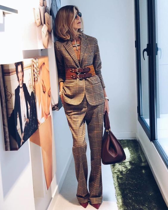 a neutral plaid pantsuit accented with a brown leather belt and a statement accessory for a bold look