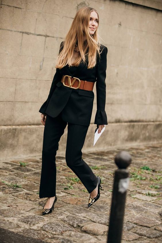 a black pantsuit with a wide brown leather belt, black embellished shoes and a statement necklace