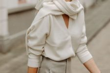 12 a white oversized cardigan paired with grey wideleg pants, a white scarf and a burgundy bag