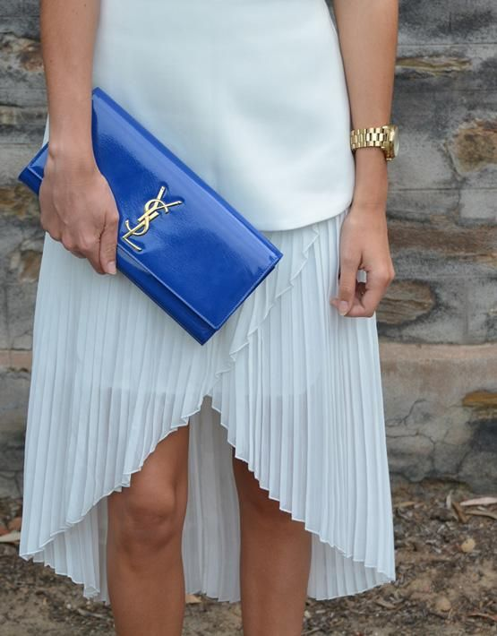 a classic blue shiny clutch with gold detailing by Yves Saint Laurent is a cool colorful statement