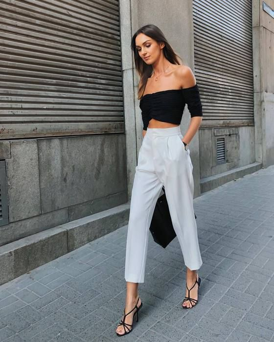 a sexy minimalist spring outfit with a black off the shoulder top, white cropped pants, black shoes and a bag