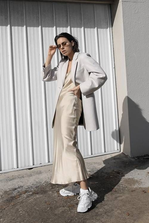 an ivory silk slip midi dress, a white oversized blazer and white trainers for a minimalist look
