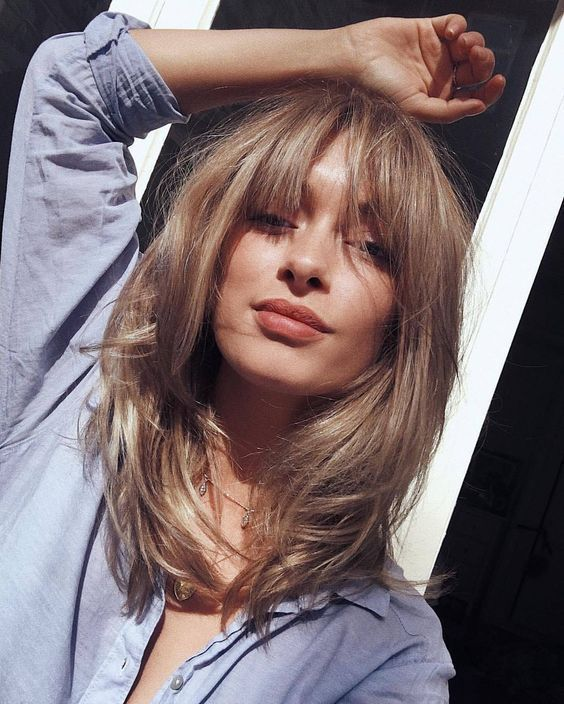 medium length soft blond layered haircut with shaggy bangs is veyr romantic