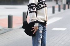 14 a graphic oversized sweater, blue ripped boyfriends, white trainers and a black bag