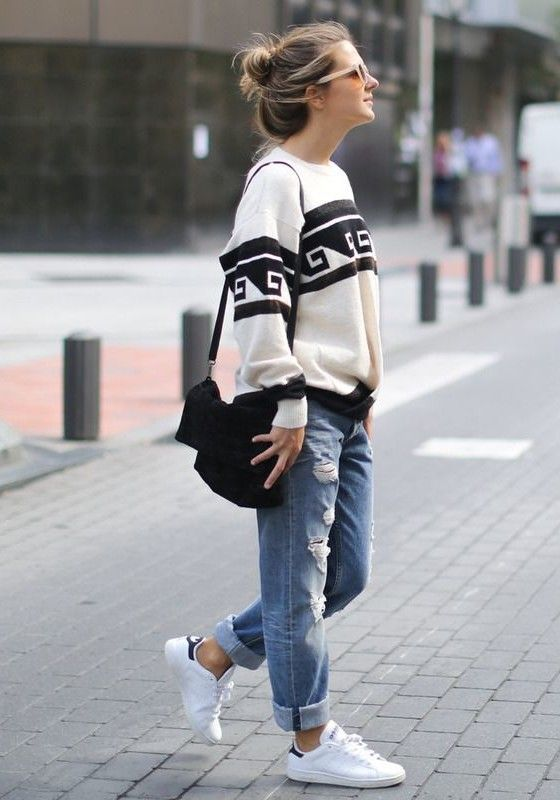 a graphic oversized sweater, blue ripped boyfriends, white trainers and a black bag