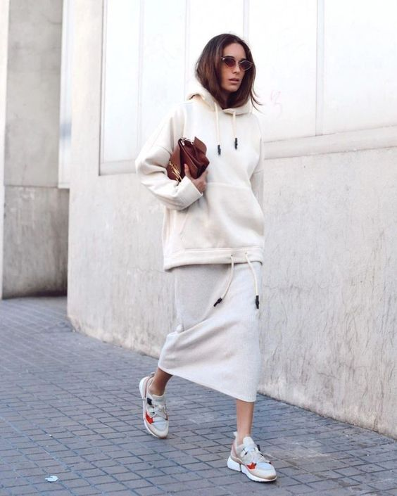 a monochromatic neutral outfit with a midi skirt, a neutral hoodie, trainers and a brown bag