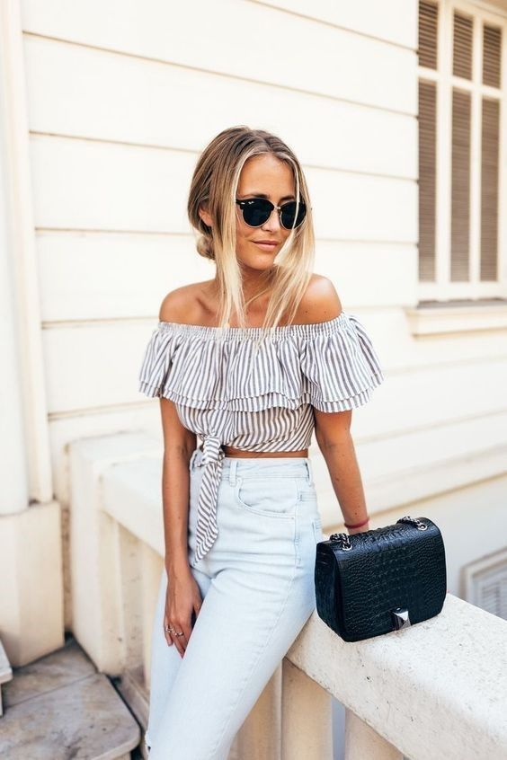a striped off the shoulder crop top features 2 trends in one, high waisted jeans and a black bag