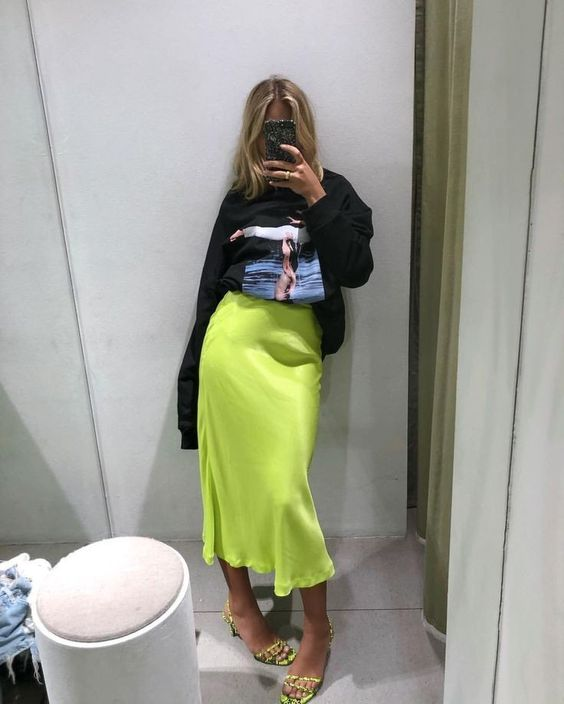 an oversized black sweatshirt, a neon green midi, neon green shoes for a hot spring look
