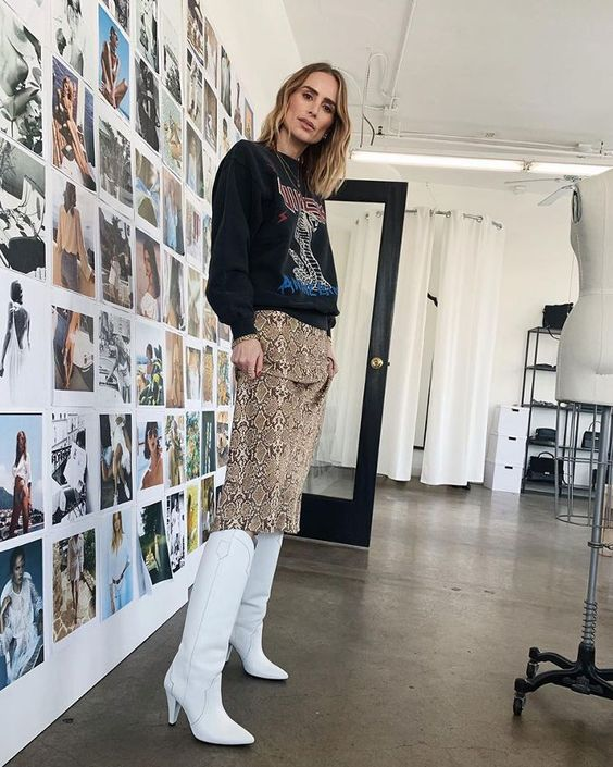 a printed black hoodie, a snakeskin knee skirt and white cowboy style boots