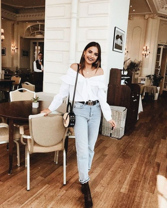 a stylish look with a white off the shoulder ruffle blouse, high waisted jeans, black booties and a two tone bag