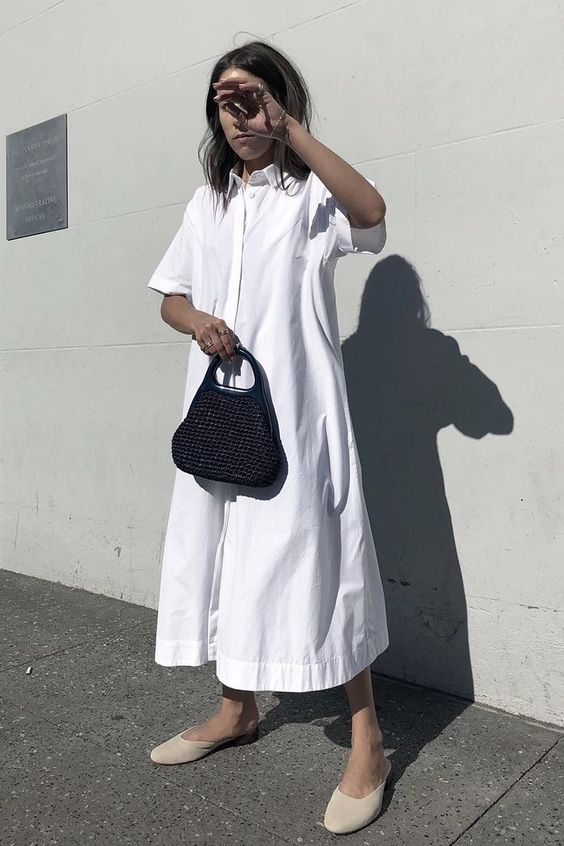 a white A-line shirtdress, ivory slippers and a black bag for a spring or summer outfit