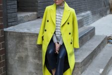 15 black leather pants, a striped grey and white sweater, black sneakers and a neon green coat