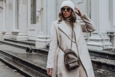 16 a cozy look with a sweater dress, a neutral coat, white sneakers, a white beanie and a brown bag