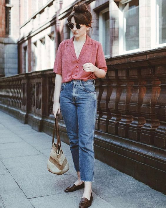 a retro-inspired outfit with a pink printed shirt, blue mom jeans, brown moccasins and a striped bag