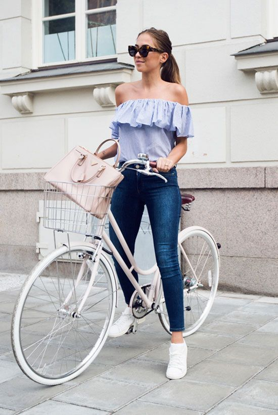 a stylish spring look with a blue off the shoulder blouse, blue skinnies, white sneakers and a blush bag