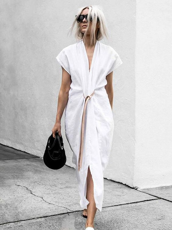 a white minimalist knot midi dress with a beige belt, cap sleeves and a black bag for summer