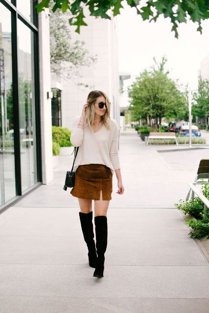 With beige loose shirt, black over the knee boots and black mini bag